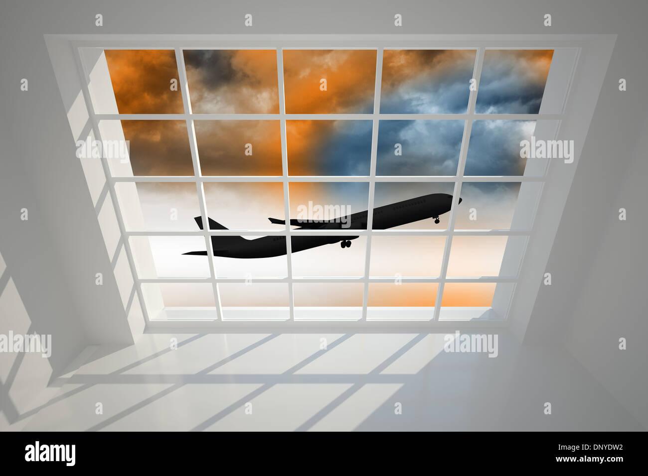 Airplane flying over orange sky past window - Stock Image