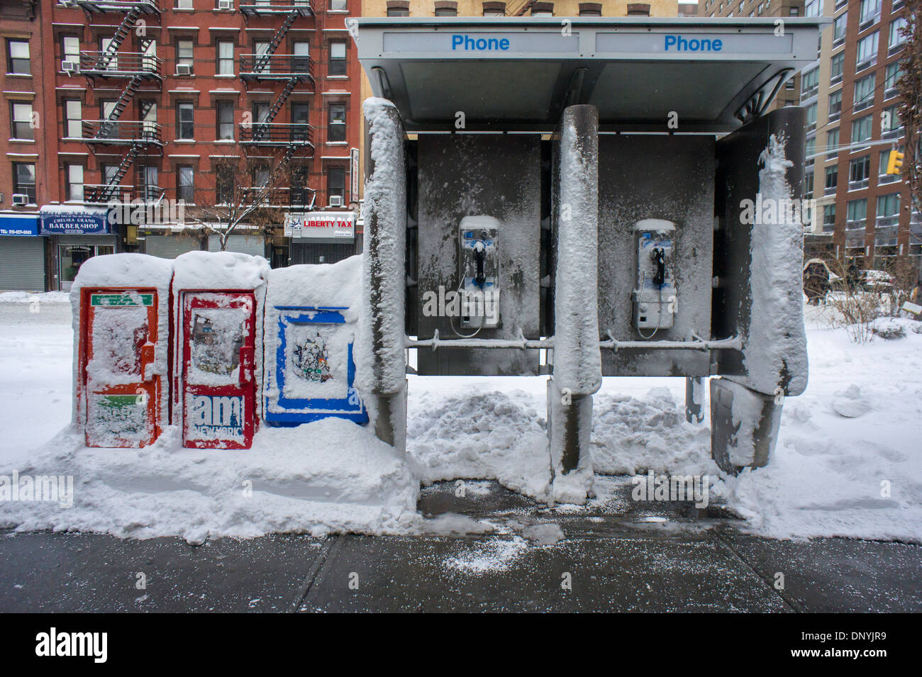 Newspaper boxes and a telephone kiosk covered with snow in the Chelsea neighborhood of New York - Stock Image