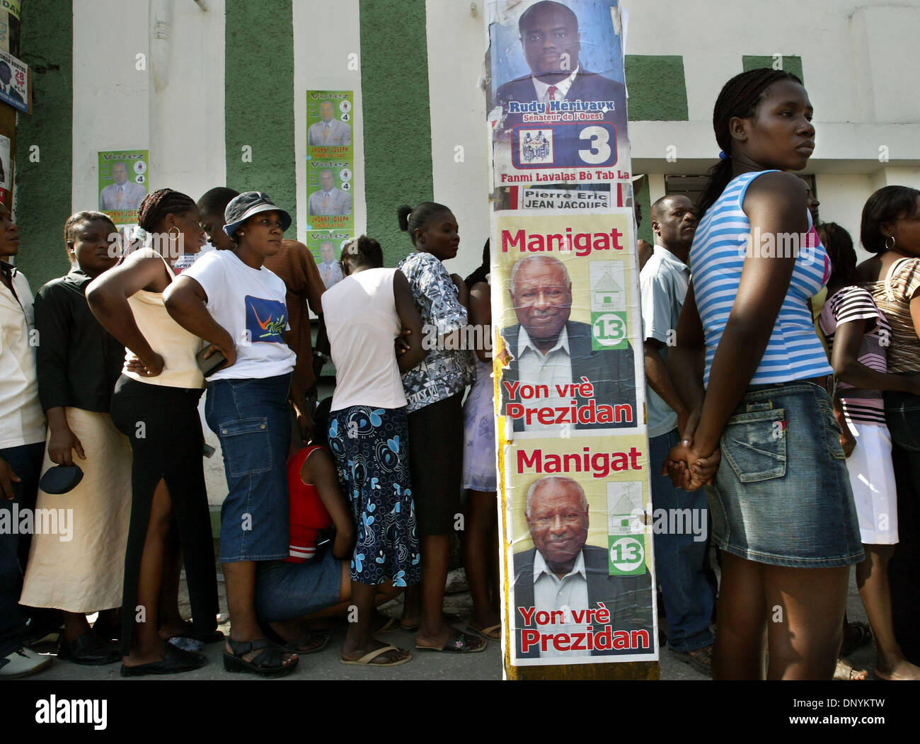 Feb 03, 2006; Port-Au-Prince, HAITI; Haitians line up to get their voting cards outside  elections headquarters Friday.   Officials say about 20% of the 3.5 million cards had not yet been distributed by midweek. Leslie Manigat, featured in one of the campaign posters on a power pole, was first elected president in January 1988, after the fall of the Duvalier regime, but was overthr - Stock Image