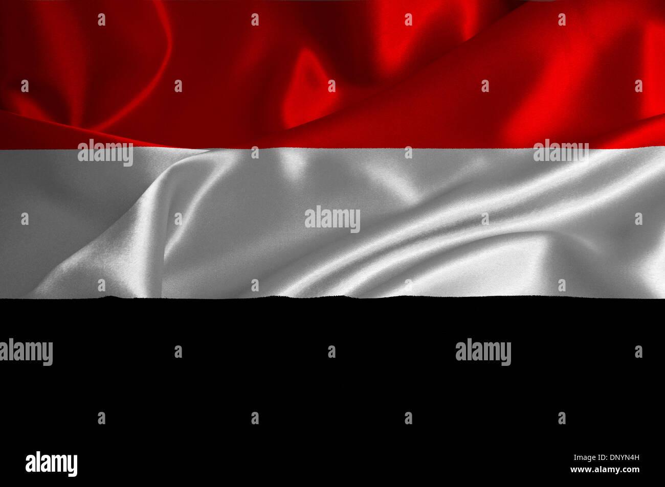 Yemen flag on satin texture. - Stock Image