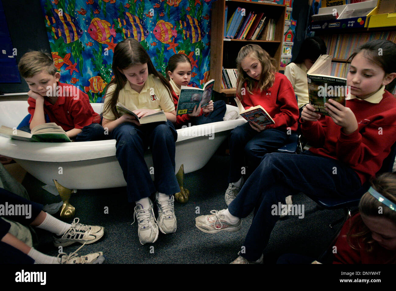 Feb 13, 2006; Shoreview, MN, USA; 'It (the tub) makes me feel like I can read anywhere,' says Vinny LaPanta, 9, as he reads above in a claw foot tub along with classmates, l-r, Alex Eckert, 9, Katie Moynagh, 9, Natalie TerEick, 10, and Nicolina Cecere, 9, in Ryan Pajak's fourth grade class at St. Odilia's Schoool in Shoreview, MN, Monday, February 13, 2006.  There are rules to havi - Stock Image