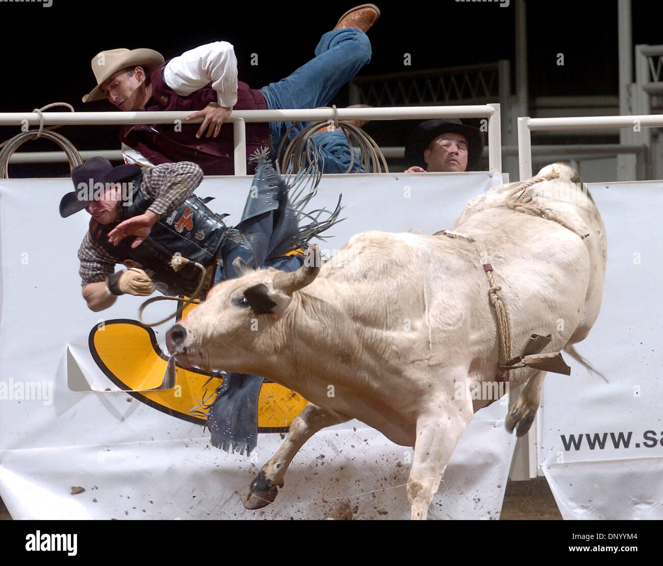 Feb 18, 2006; San Antonio, TX, USA; Cowboys jump out of the arena as Ardie Maier of Timberlake, South Dakato gets thrown off his ride during the bull riding competition at the rodeo Saturday night.  Mandatory Credit: Photo by T.R./San Antonio Express-News/ZUMA Press. (©) Copyright 2006 by San Antonio Express-News - Stock Image