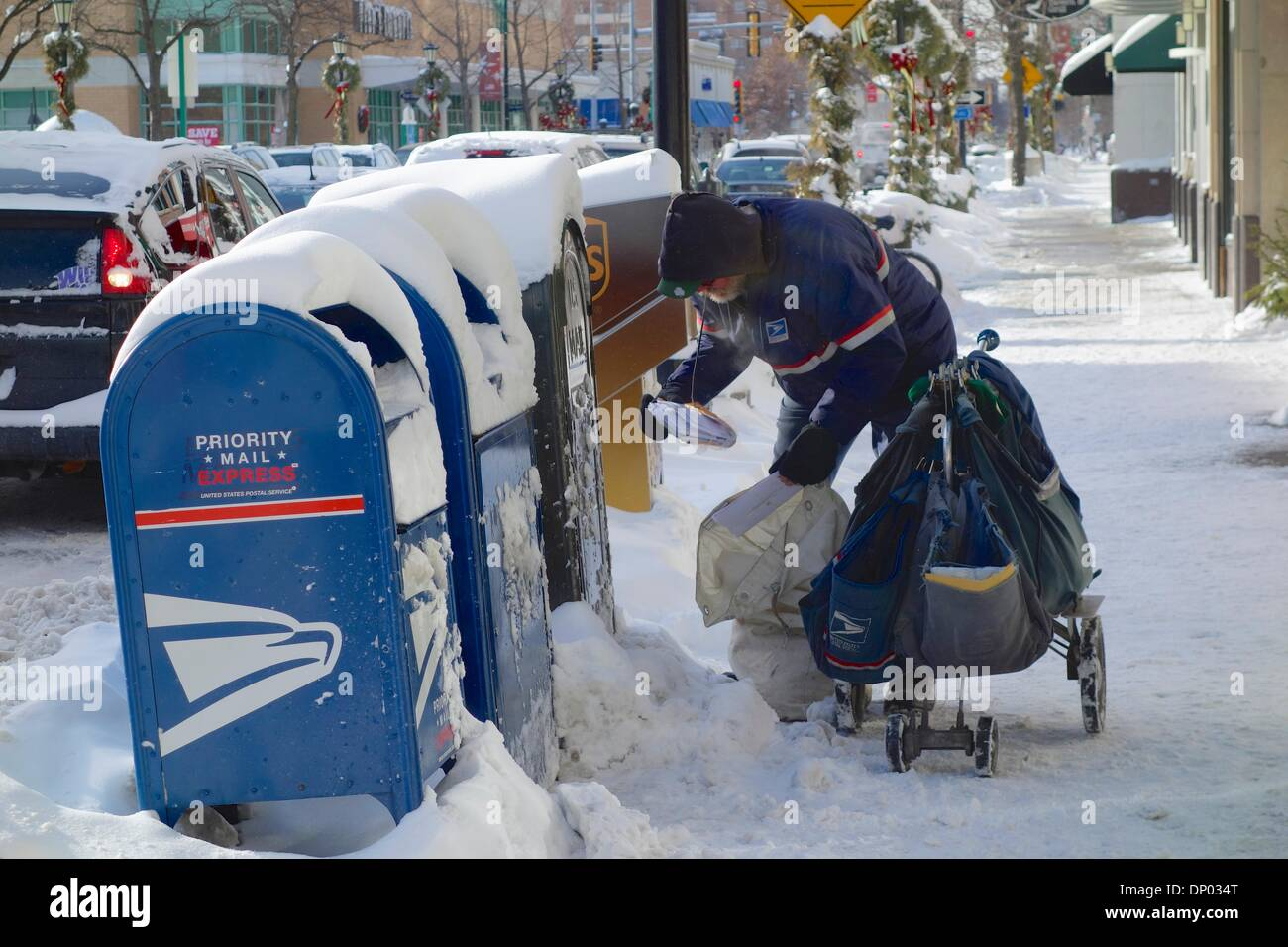 Oak Park, Illinois USA. 6th January 2014. A U.S. Postal Service letter carrier gathers mail from collection boxes along Lake Street at a brutally cold outside temperature of -11ºF/-23ºC. Credit:  Todd Bannor/Alamy Live News - Stock Image