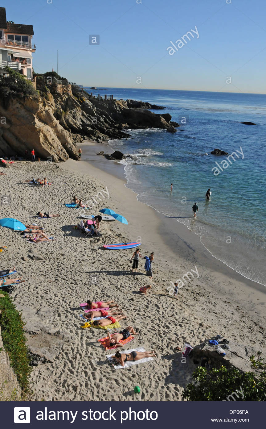Coastal homes and sun bathers at Woods Cove in Laguna Beach on a warm winter day in  Southern California Stock Photo