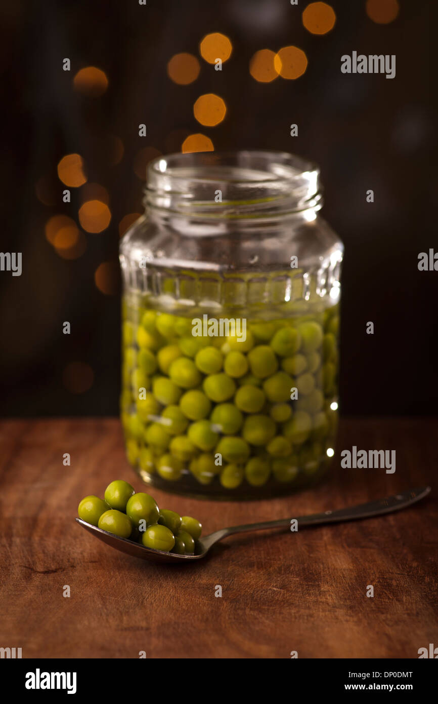 Open Glass jar of preserved peas on the dark background - Stock Image