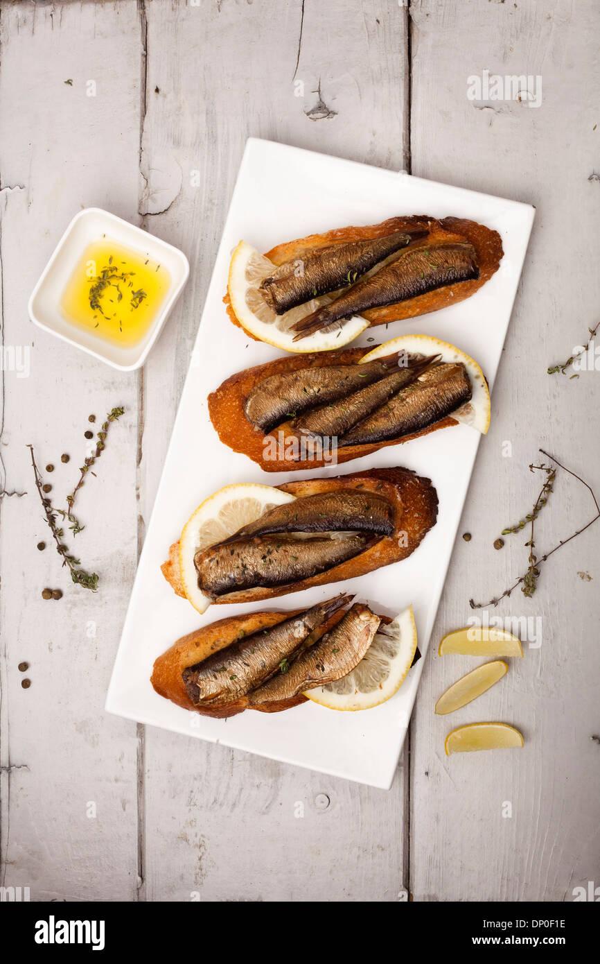 Fish, Spanish tapas - sprat with lemon on baked bread - Stock Image