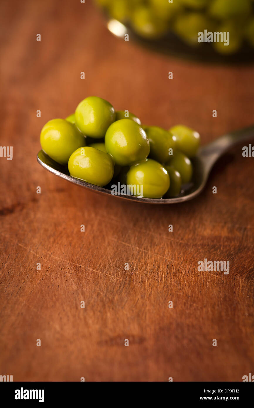 Open Glass jar of preserved peas on the dark background Stock Photo