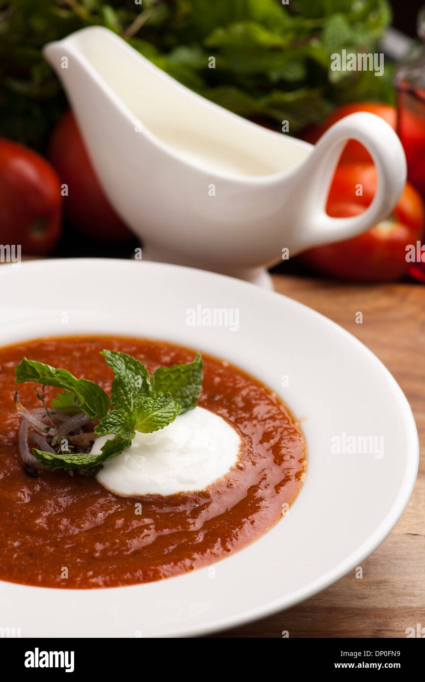Bowl of roasted delicious tomato soup, garnished with herbs and roasted onion, served with creme - Stock Image