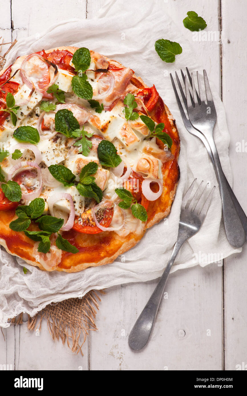 Homemade vegetarian pizza with cottage cheese and tomatoes garnished with mint - Stock Image