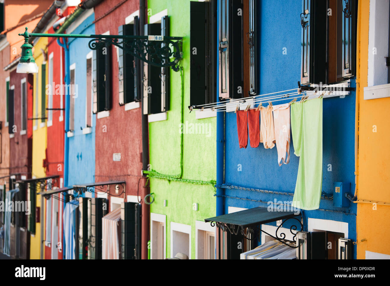 Burano, Venice - Italy; drying towels at the facade of multicolored houses - Stock Image