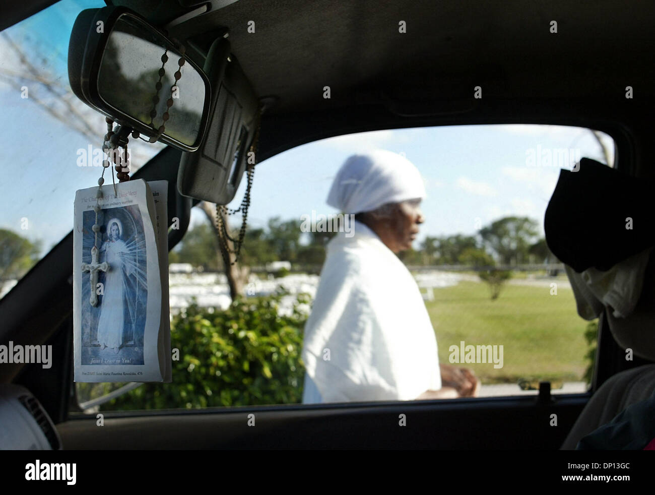 Apr 14, 2006; Delray Beach, FL, USA; One of the mourning women walks past a truck with an image of Christ and a rosary hanging from the rear-view mirror as she prepares to embark on a living Stations of the Cross with other members of Our Lady of Perpetual Help Catholic Haitian Mission in remembrance of Good Friday.  Mandatory Credit: Photo by Chris Matula/Palm Beach Post/ZUMA Pres - Stock Image