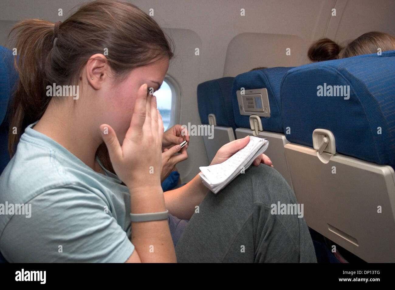 Apr 15, 2006; New Orleans, LA, USA; Emily Arthur, a student at Fresno State University, wipes away a tear as she reads a notebook filled with comments by her fellow disaster relief volunteers. During their volunteer assignment with Habitat for Humanity in the New Orleans area, her group was assigned to write in each other's notebooks at least once during the week, but they weren't  - Stock Image
