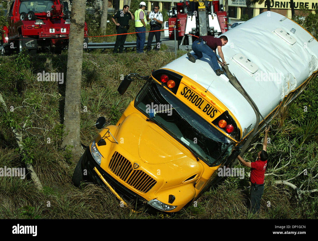 May 01, 2006; Ft. Pierce, FL, USA; Tri-County Automotive employee Anthony DiFrancesco (on top of bus) working with fellow employee Pete Bordonali, right, works to attach a harness around the mid-section of a school bus that drove off the Okeechobee Road I-95 southbound onramp monday morning.  Heavy duty chains were attached to the harness and bus- two heavy duty wreckers were used  - Stock Image