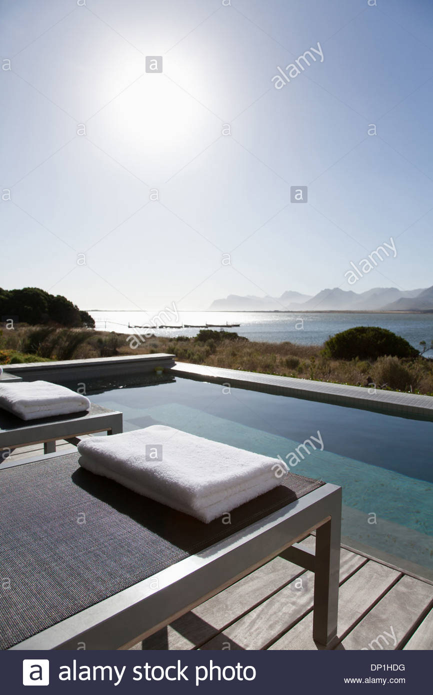 View of sun shining on lake from patio with swimming pool Stock Photo