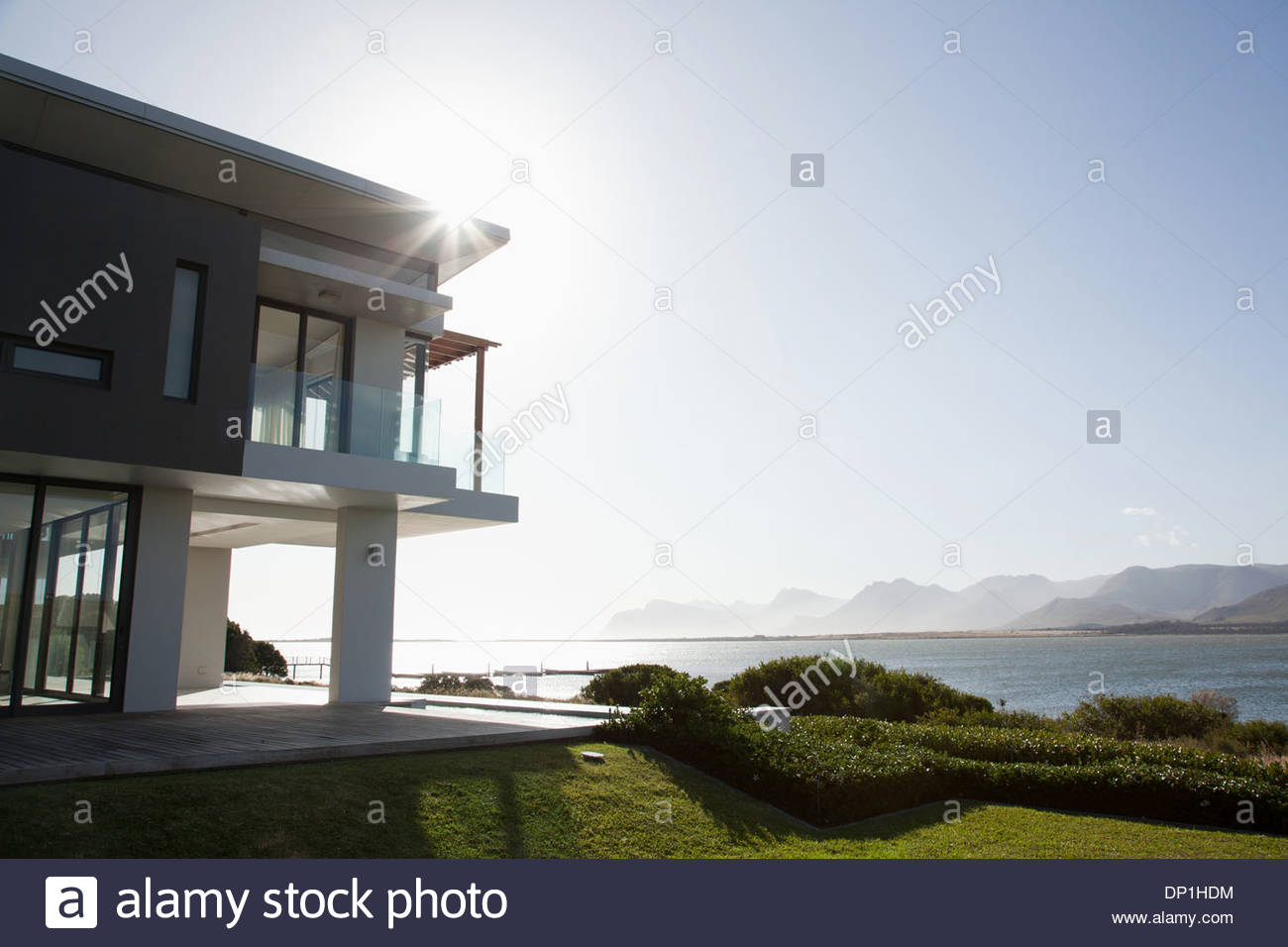 Sun shining over lake and modern house - Stock Image