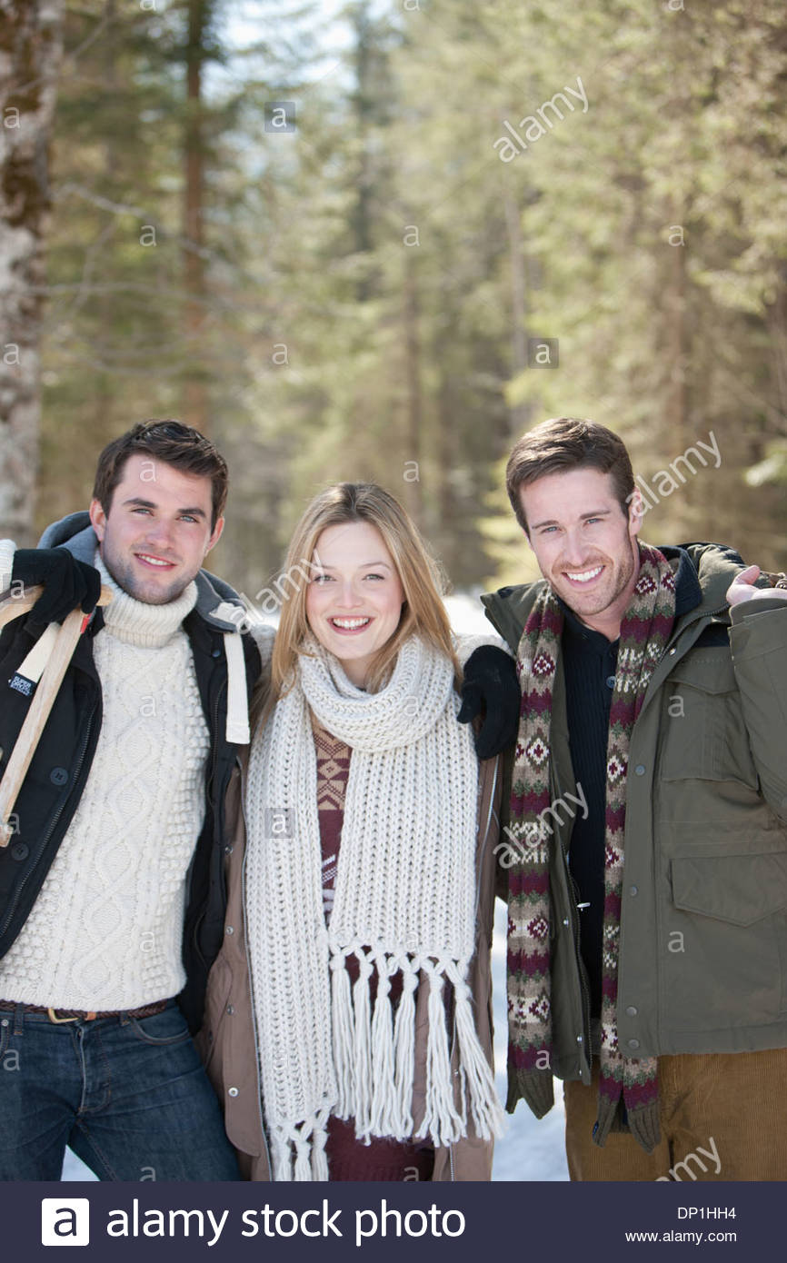 Portrait of friends holding sleds in snowy woods - Stock Image