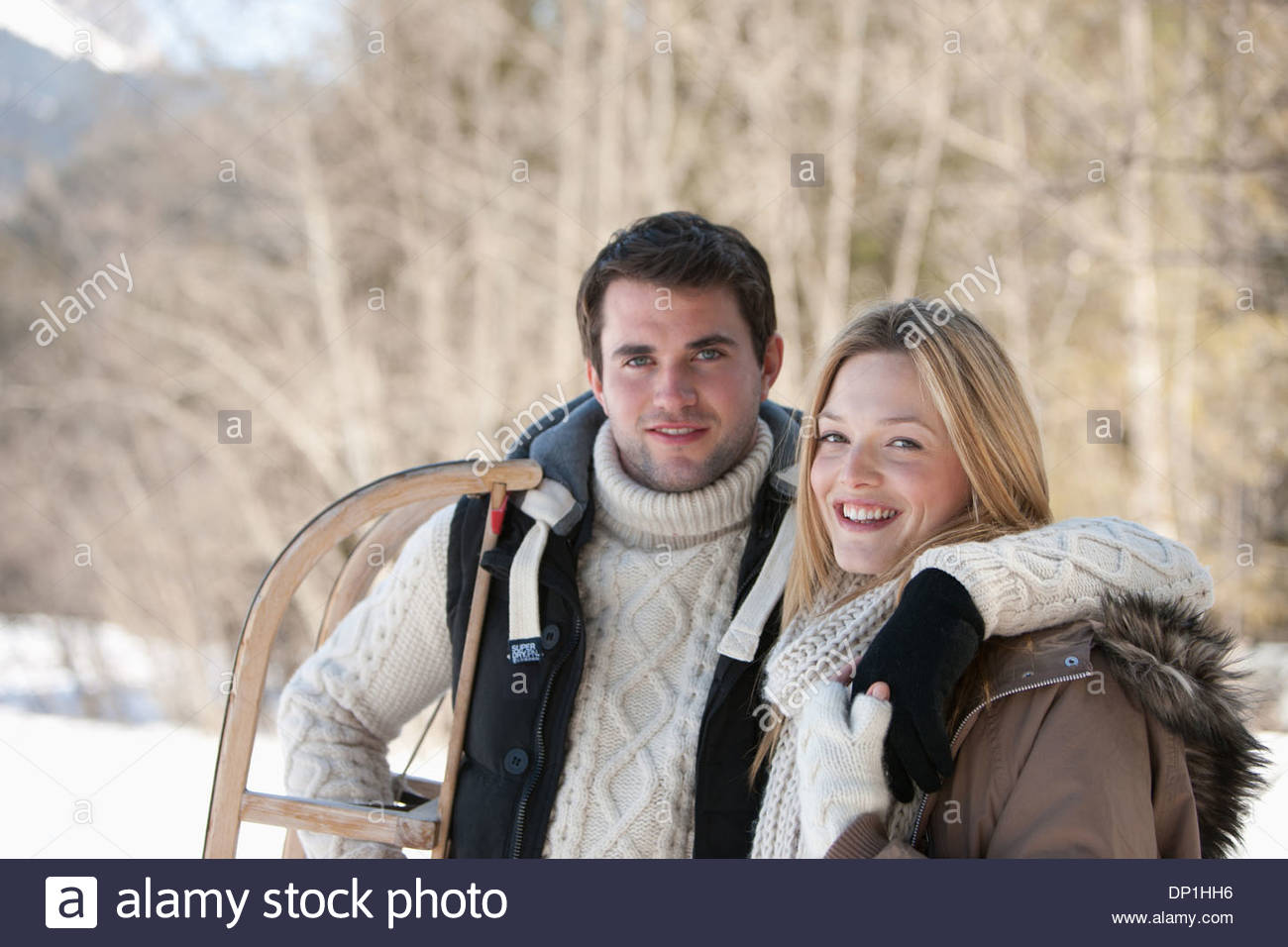 Portrait of smiling couple with sled in woods - Stock Image