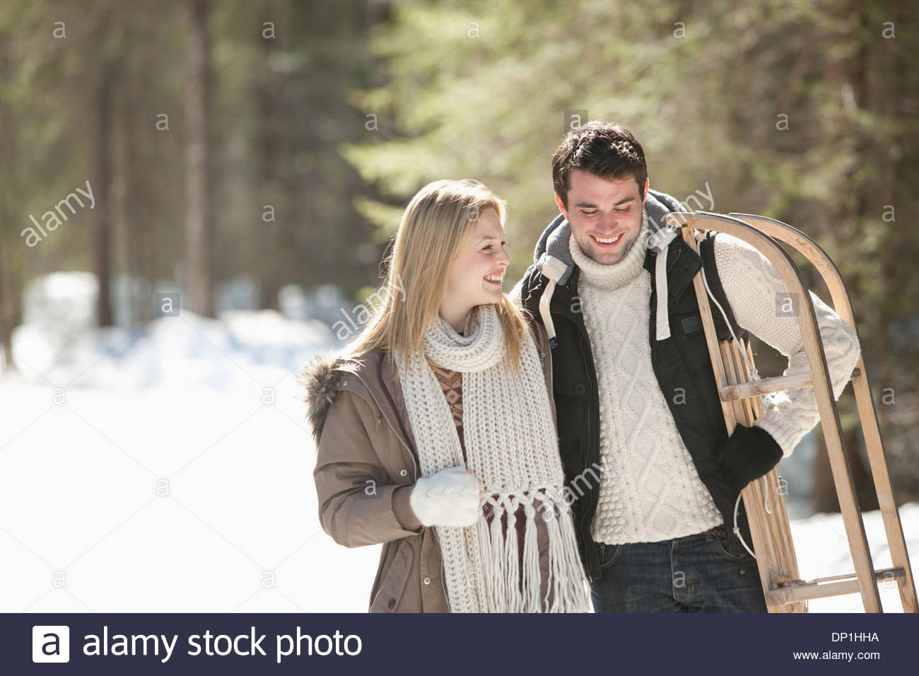 Smiling couple with sled walking in snowy woods - Stock Image