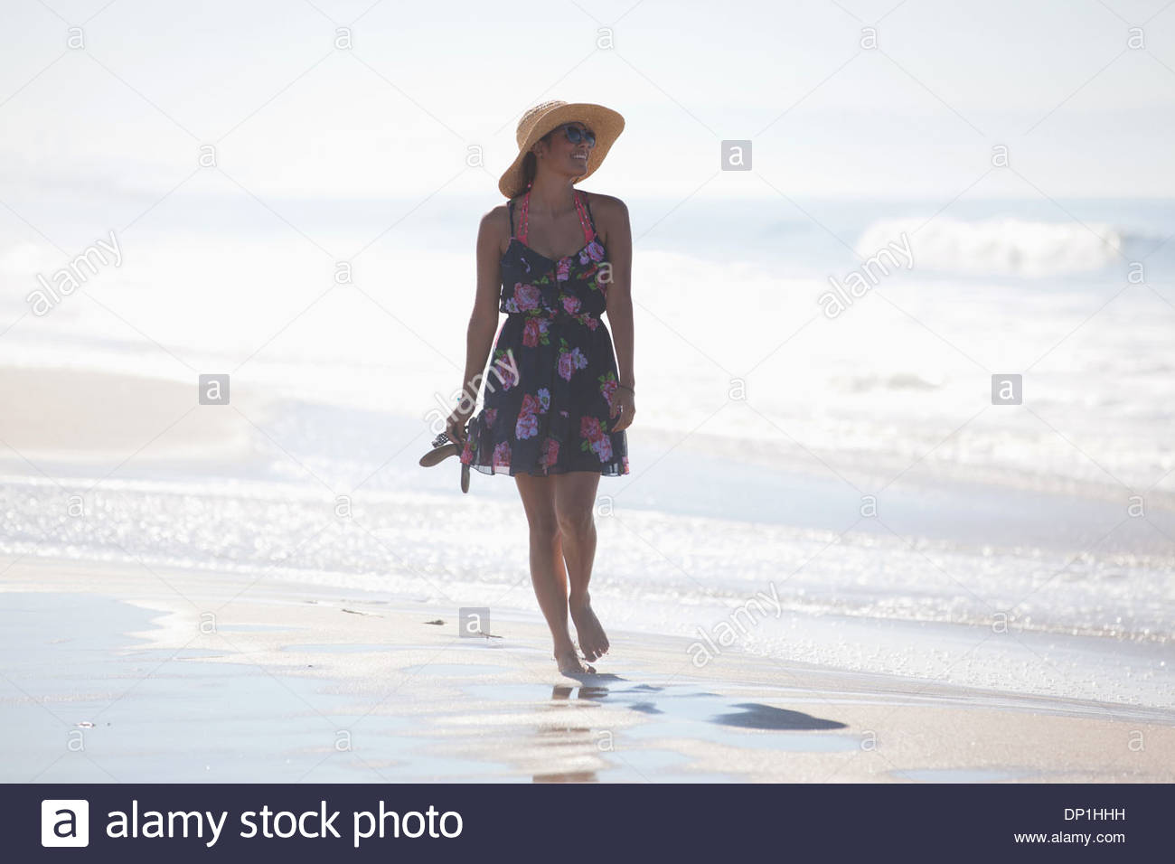 Woman carrying sandals on beach - Stock Image