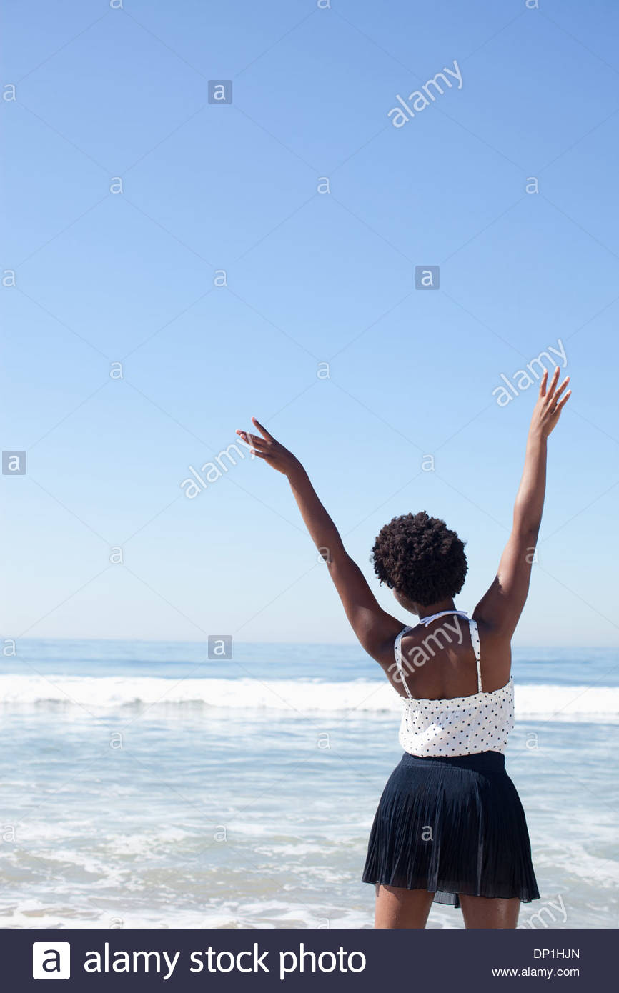 Woman posing in waves on beach - Stock Image