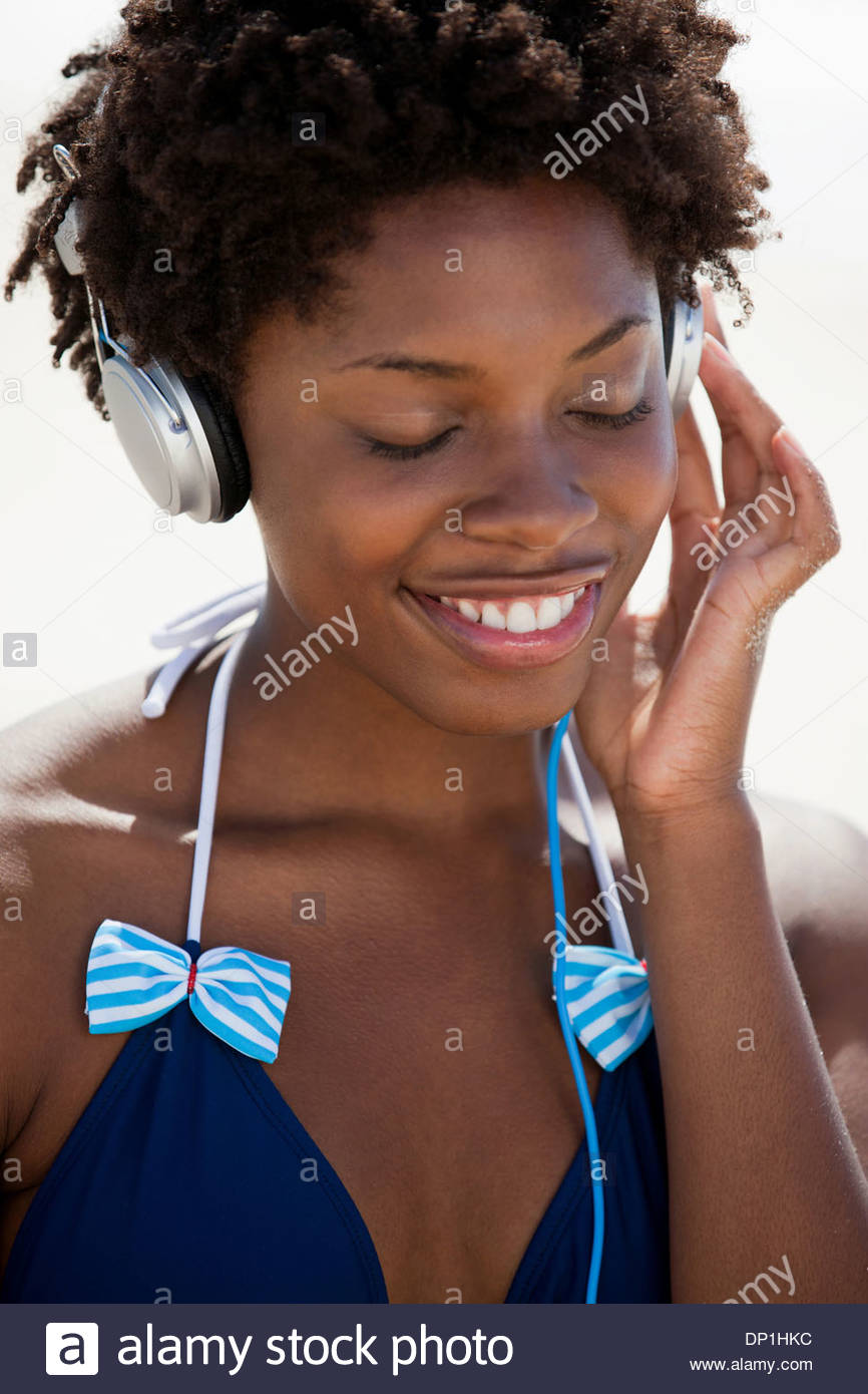 Woman listening to music on headphones - Stock Image
