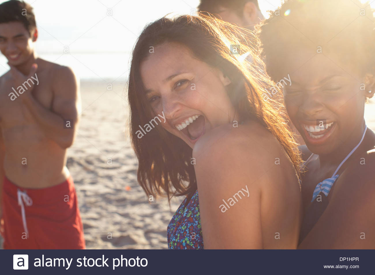 Women playing together on beach - Stock Image