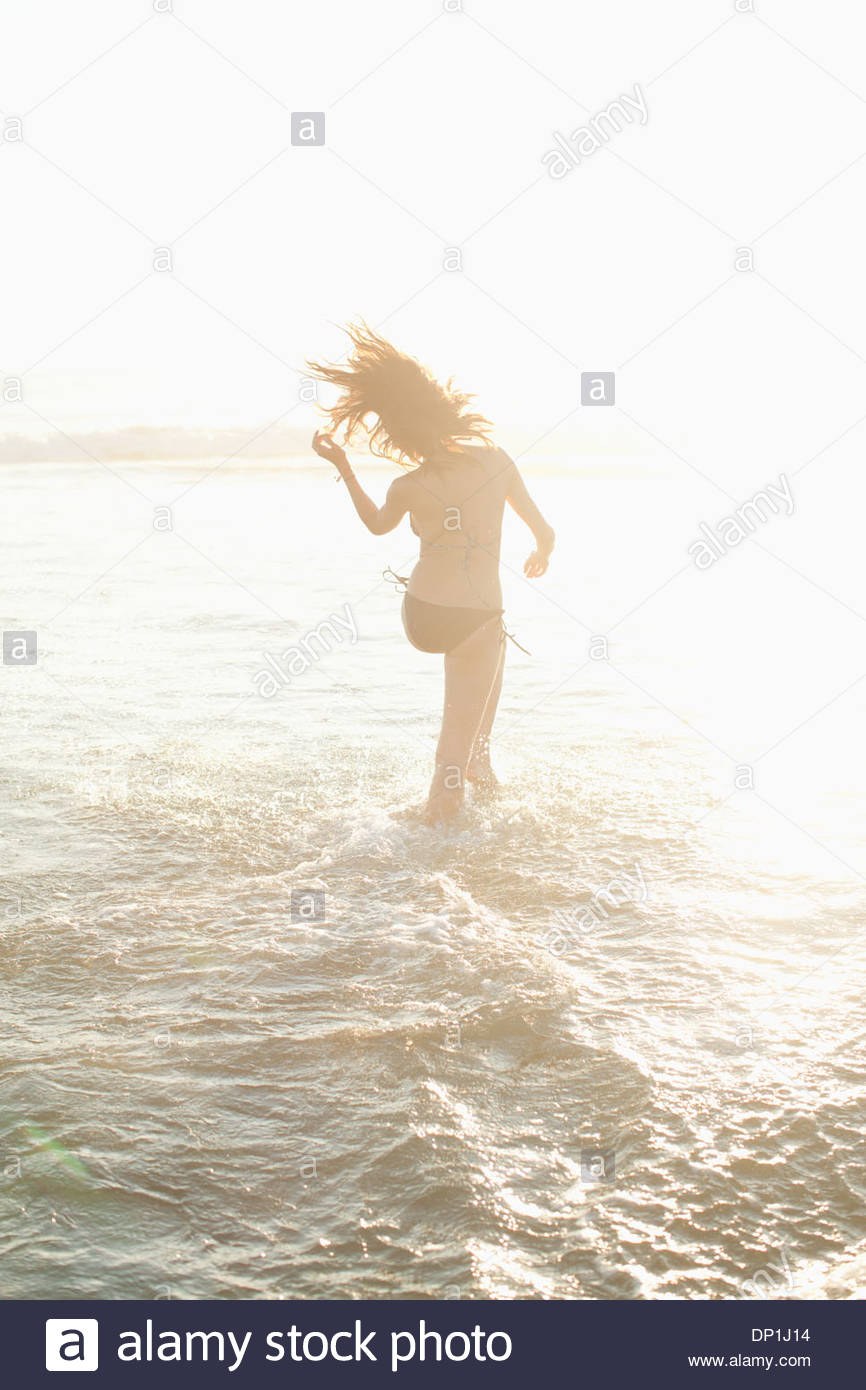 Woman walking in waves on beach - Stock Image