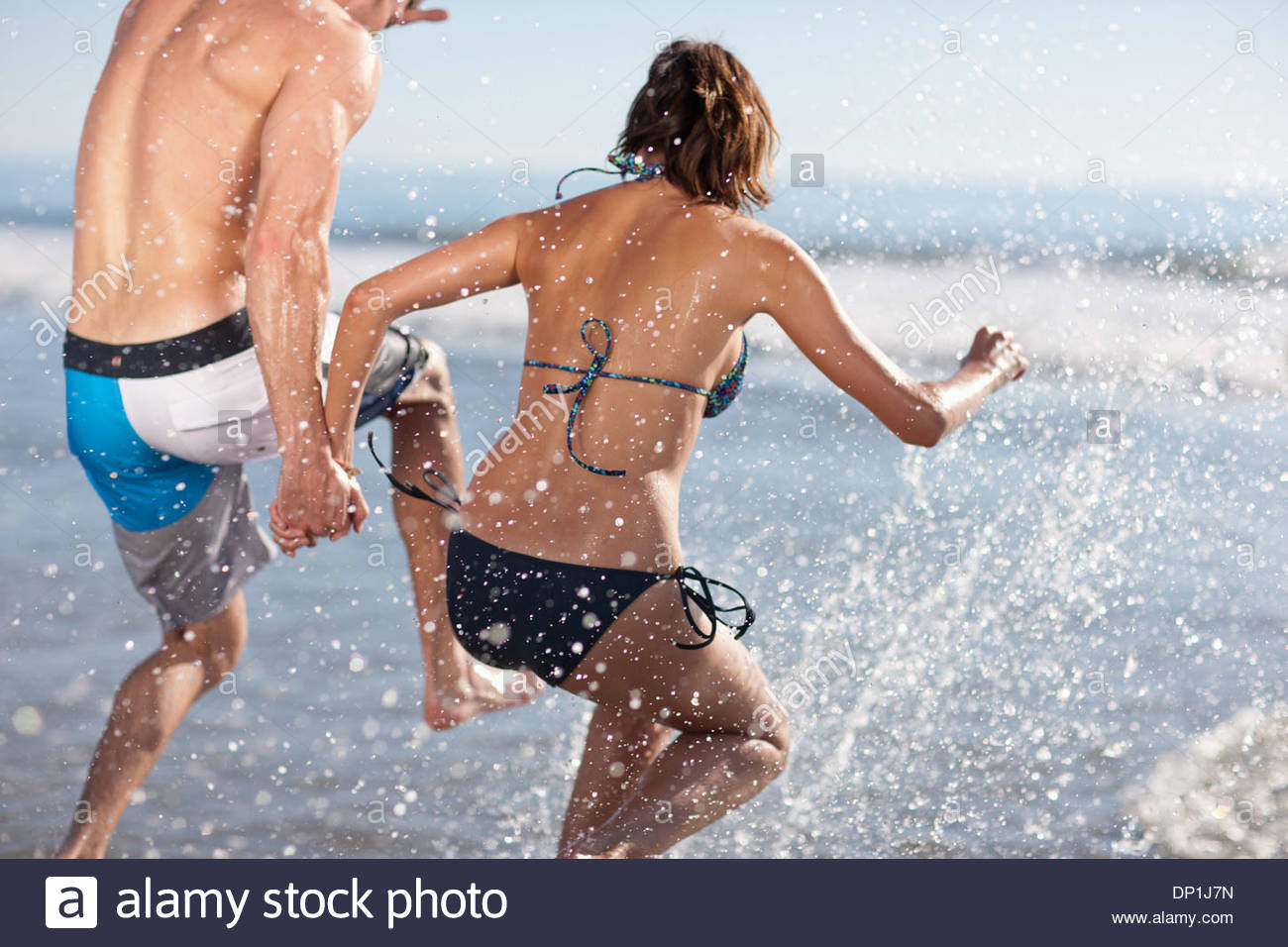 Couple playing in waves on beach Stock Photo