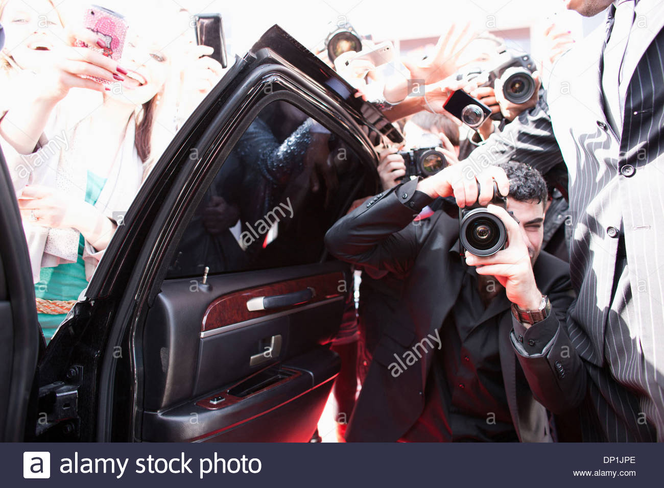 Paparazzi taking pictures of celebrity in car Stock Photo