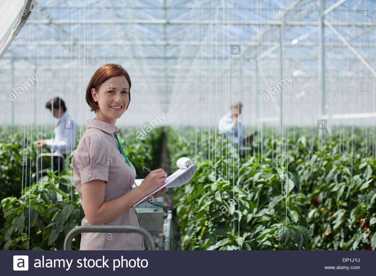 Woman writing on clipboard in greenhouse - Stock Image