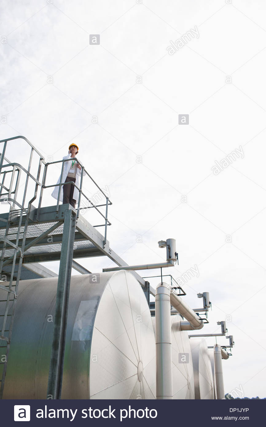 Scientist atop industrial tank - Stock Image