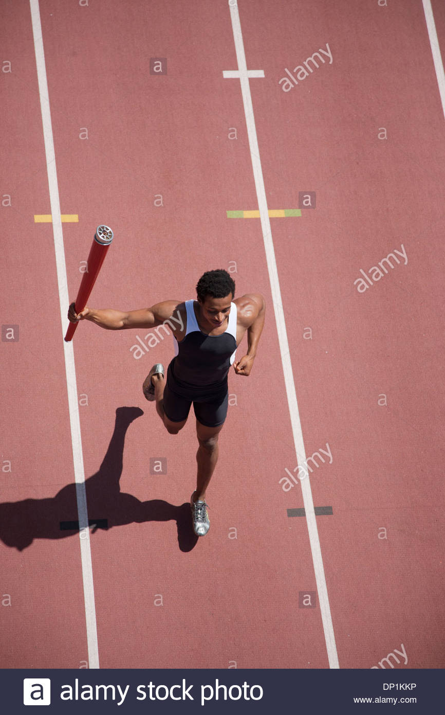 Runner running with torch on track - Stock Image