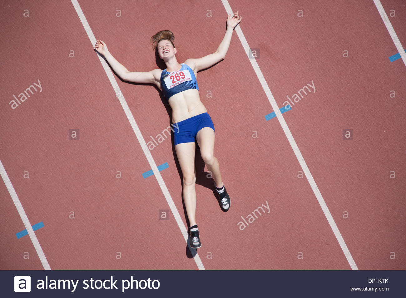 Tired runner laying on track - Stock Image