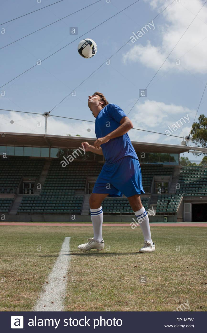 Soccer player heading soccer ball - Stock Image