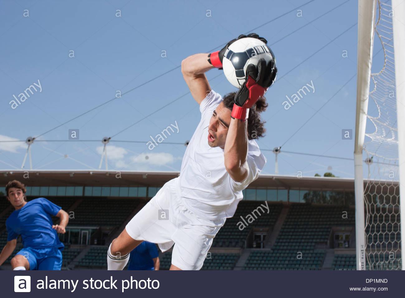 Soccer goalie catching soccer ball - Stock Image