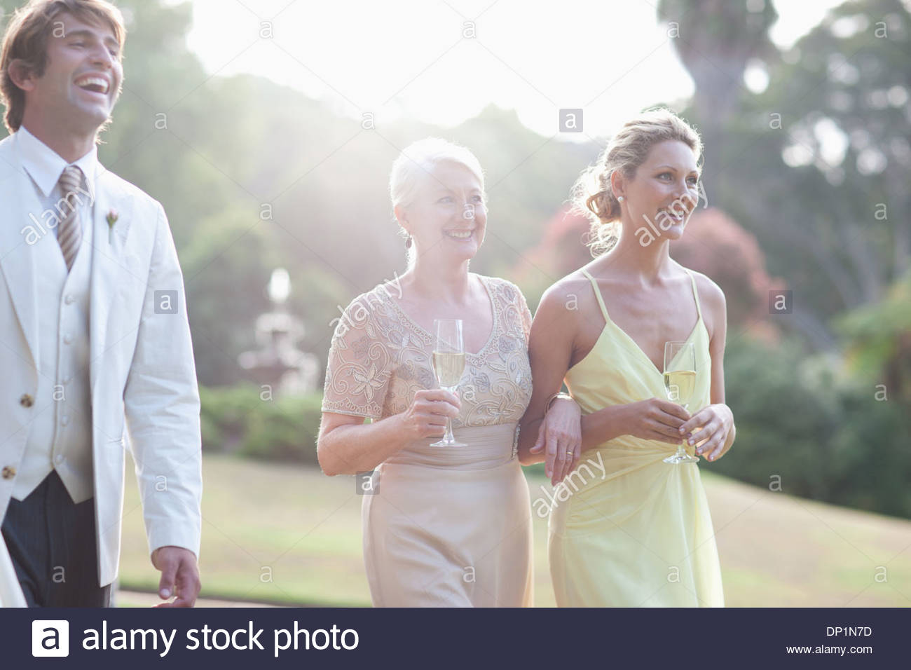Wedding guests walking across lawn - Stock Image
