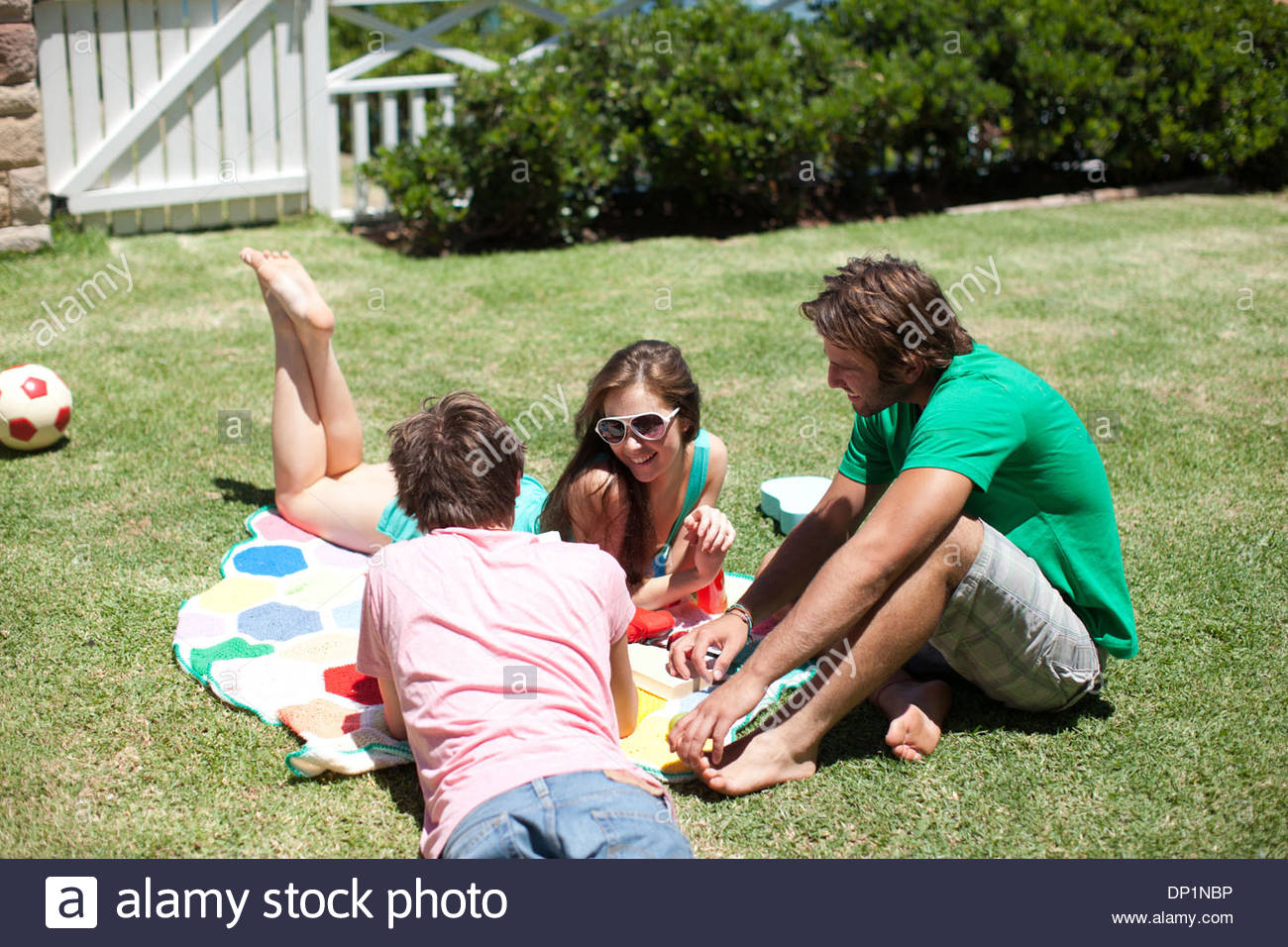 Friends relaxing with books and drinks on blanket in sunny grass - Stock Image