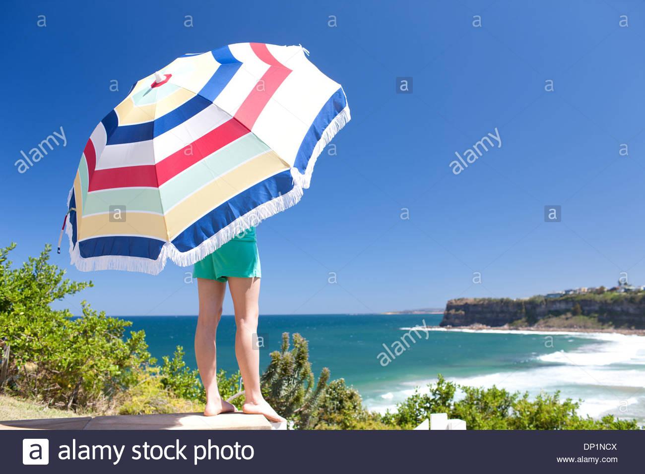 Woman in beach holding umbrella - Stock Image
