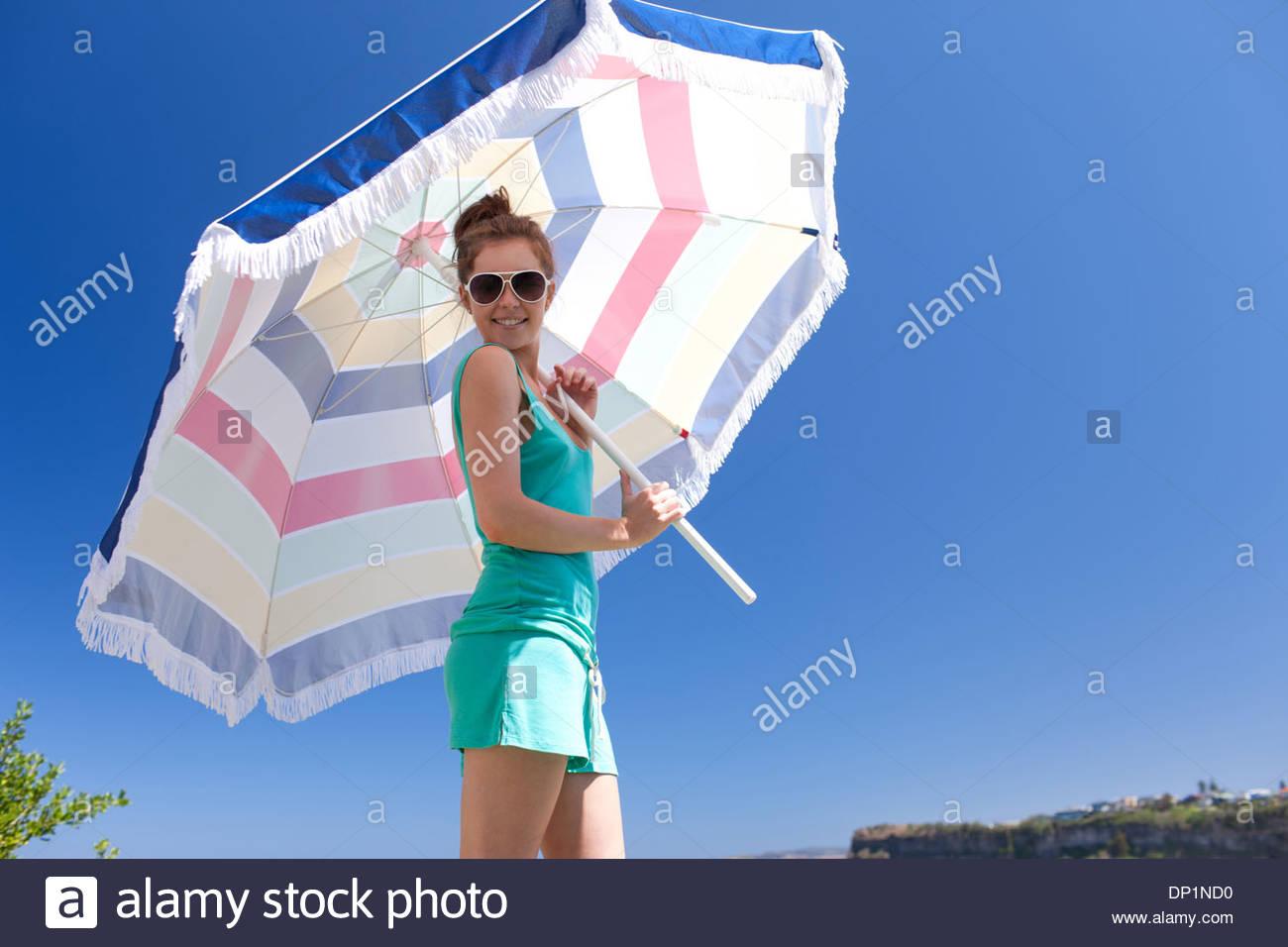 Woman in sunglasses holding beach umbrella - Stock Image