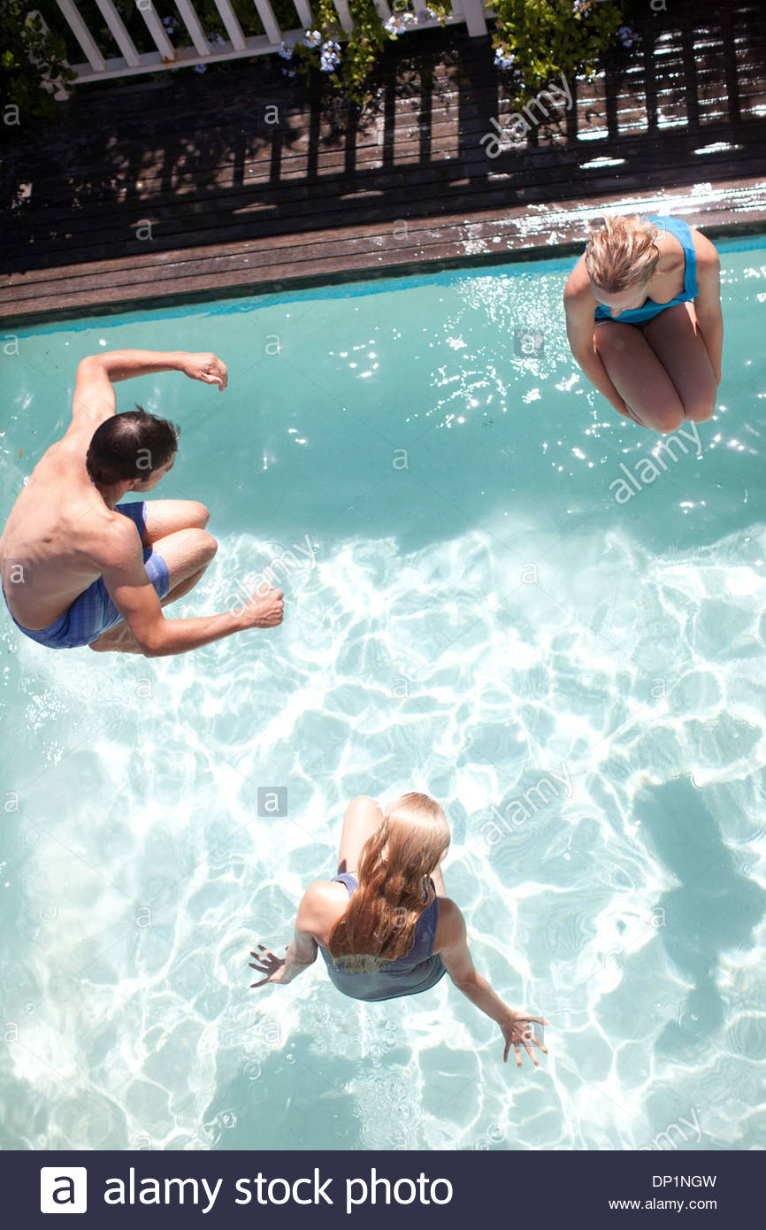 Friends jumping in swimming pool - Stock Image
