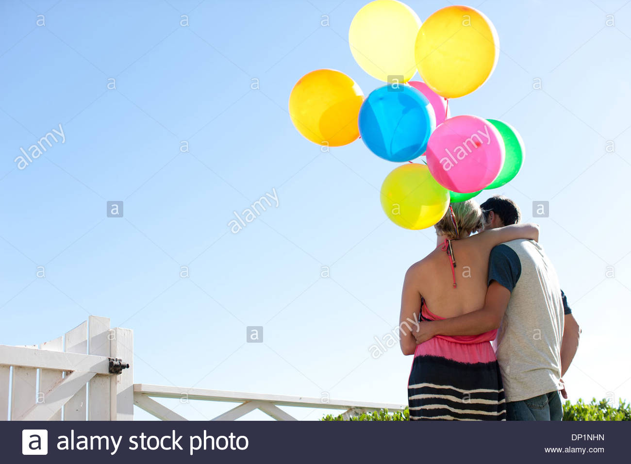 Couple with balloons hugging - Stock Image