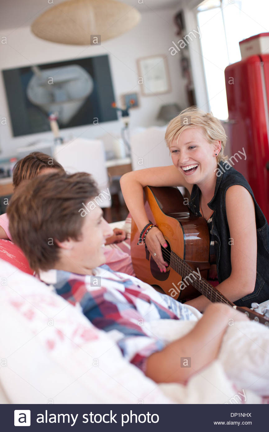 Woman with bare feet playing guitar for men on sofa - Stock Image