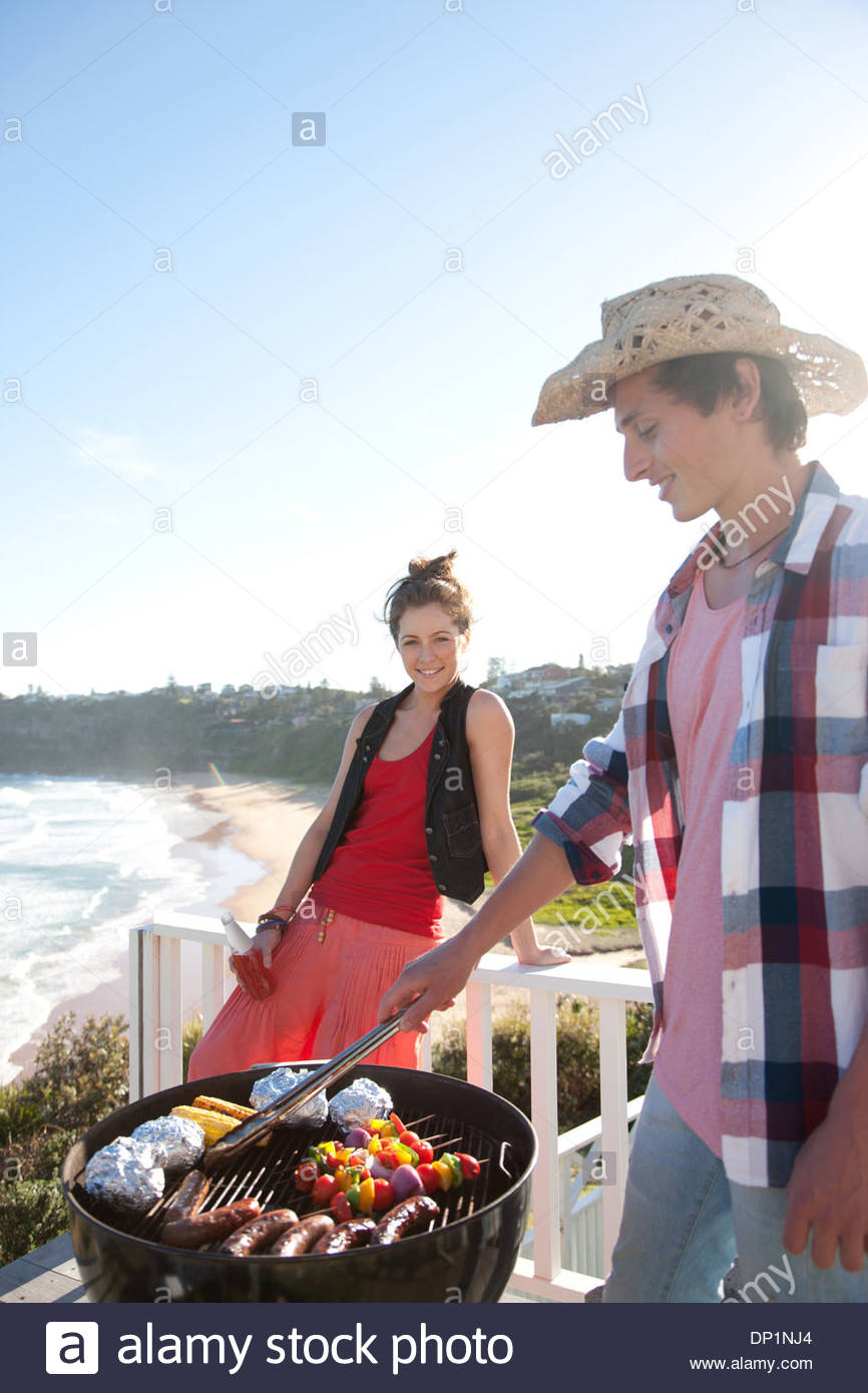 Man and woman tending barbecue with ocean in background - Stock Image