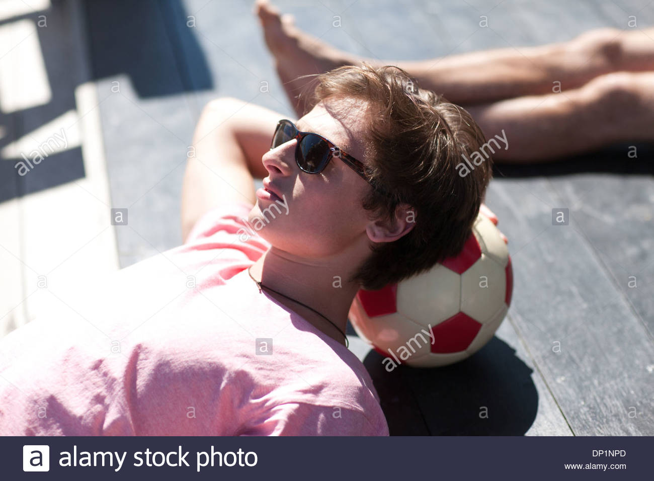 Man resting head on soccer ball - Stock Image