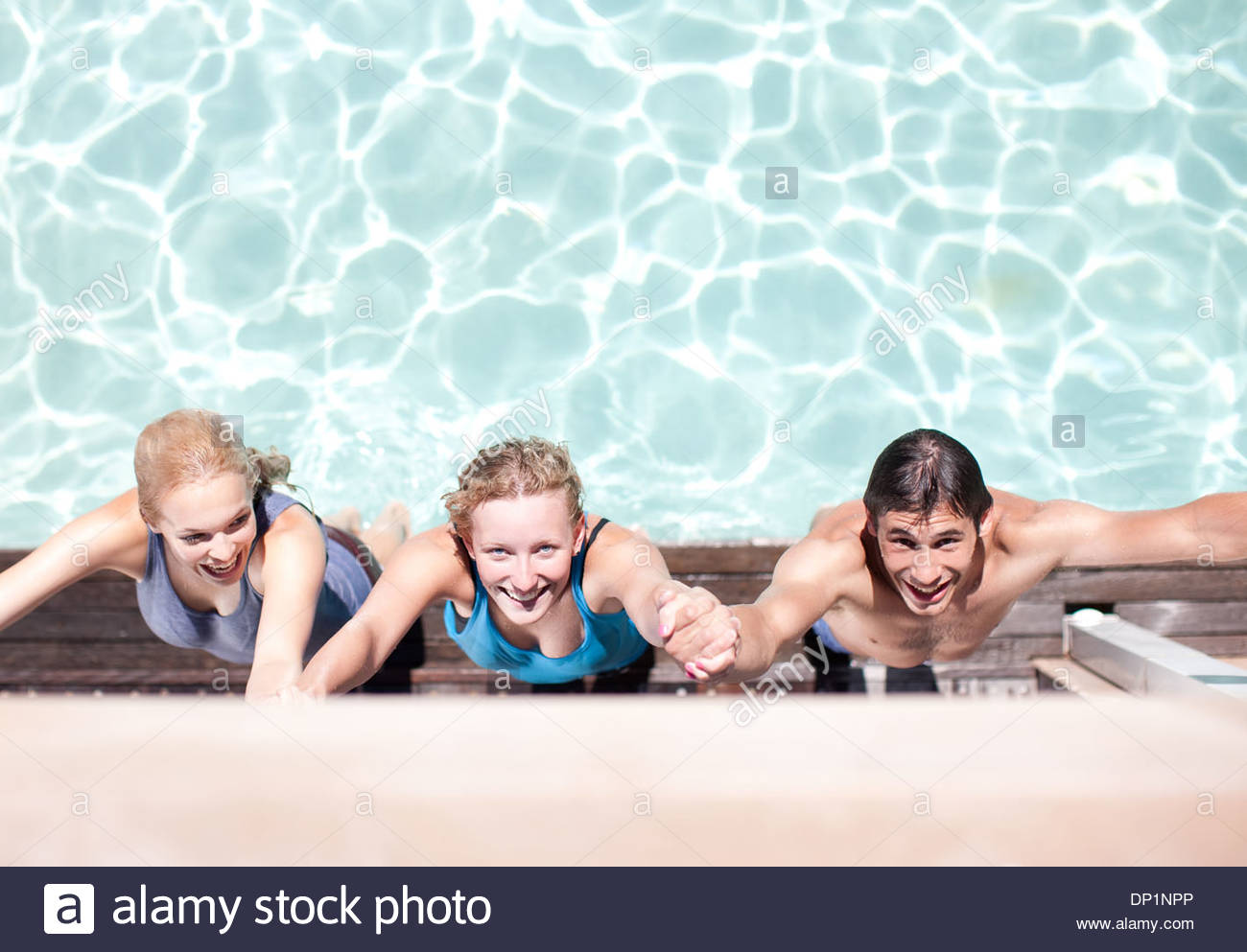 Friends beside swimming pool - Stock Image