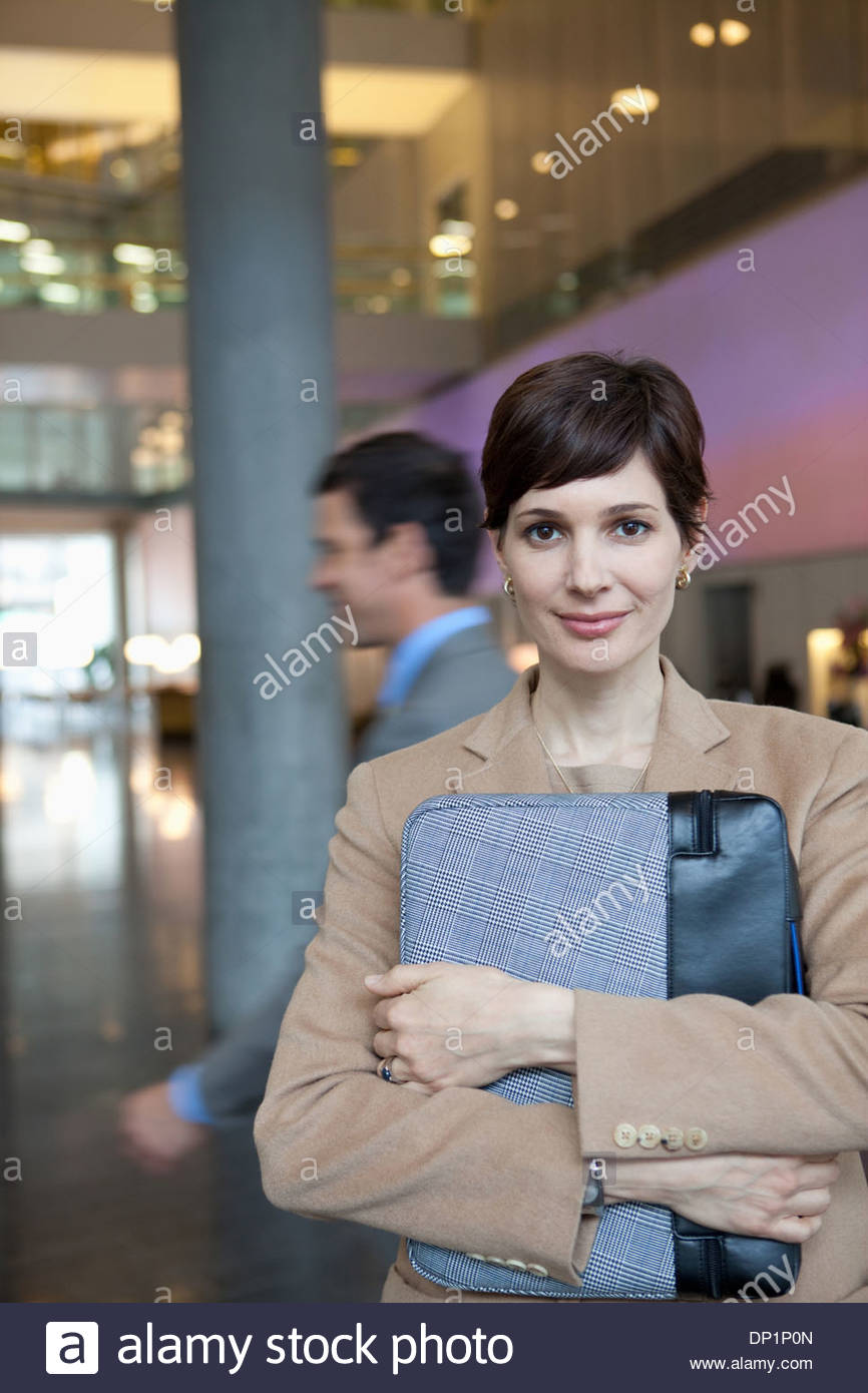 Smiling businesswoman holding briefcase - Stock Image