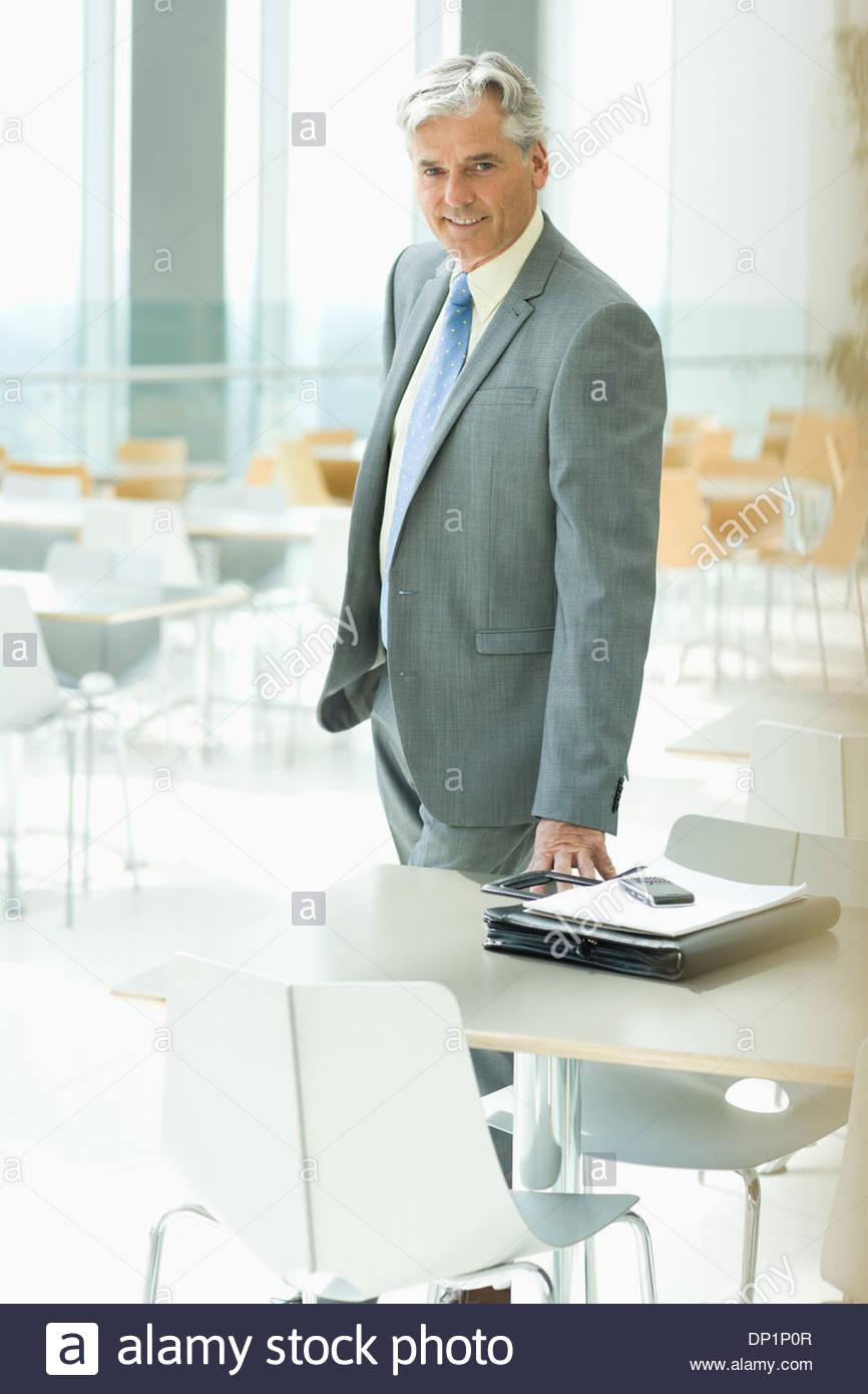Smiling businessman in cafeteria - Stock Image