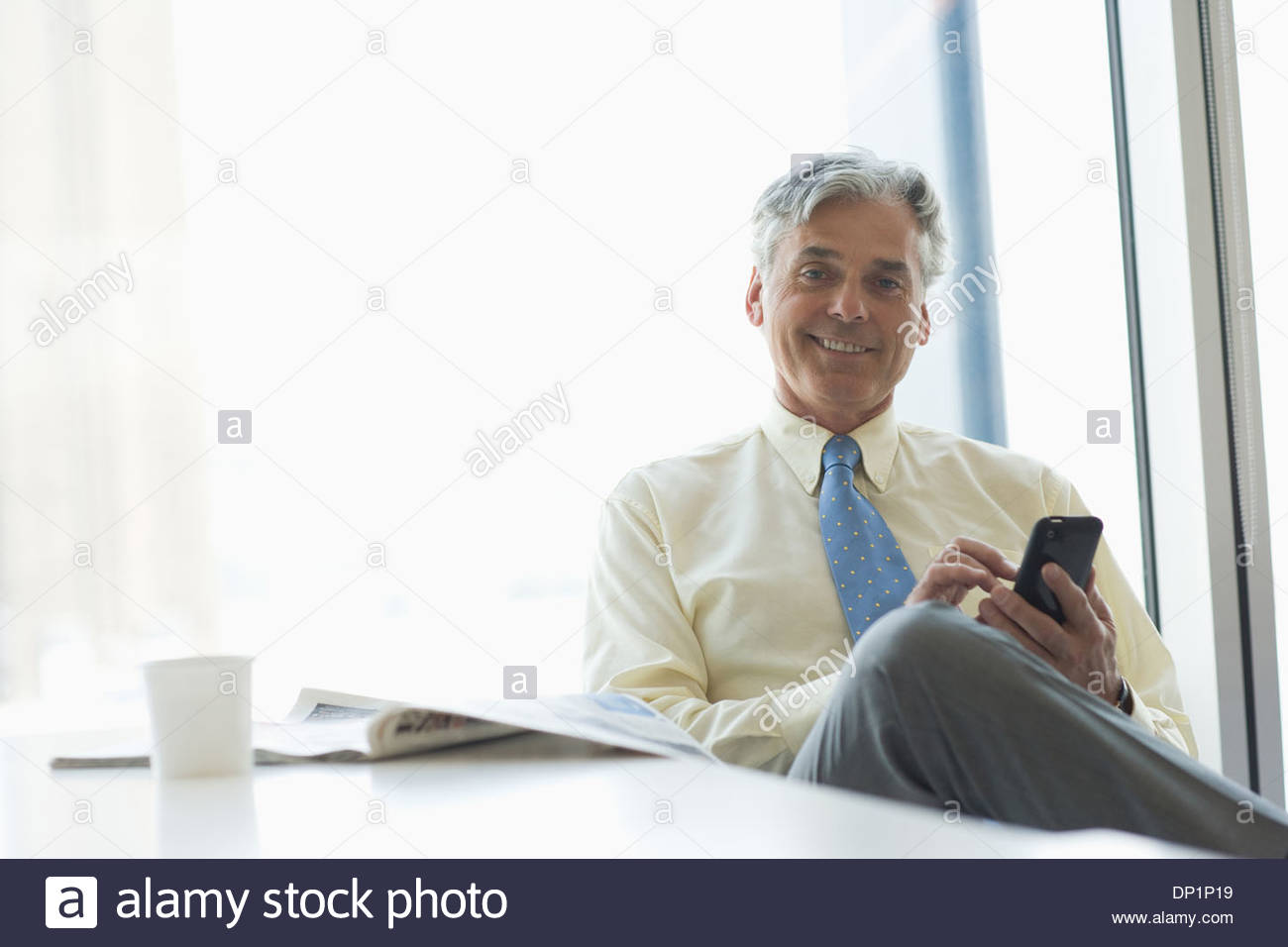 Businessman text messaging on cell phone in cafeteria - Stock Image