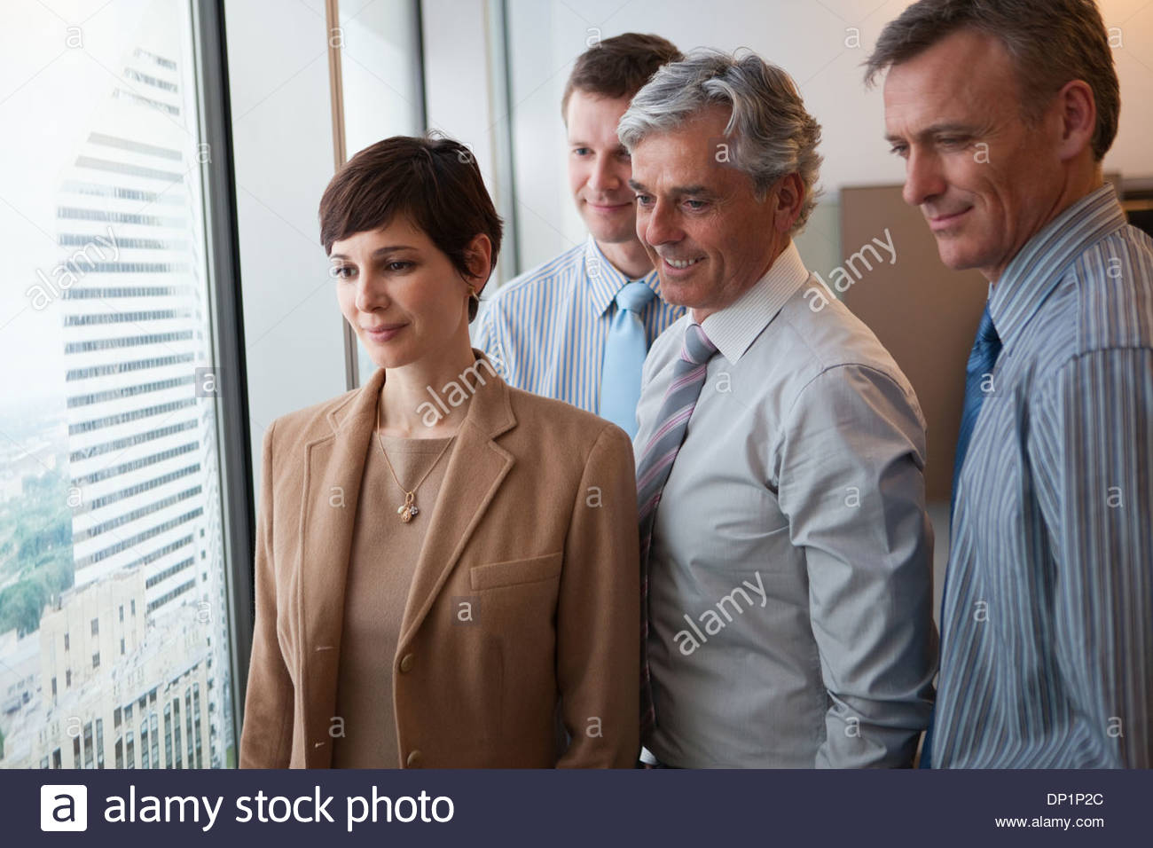 Businesspeople looking out window - Stock Image