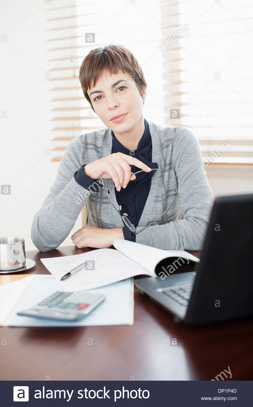 Businesswoman working at desk - Stock Image